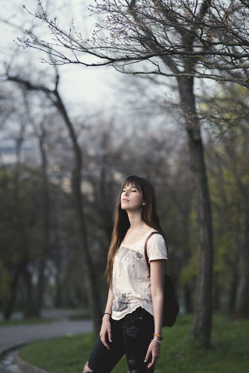Woman Standing Against Bare Trees At Park