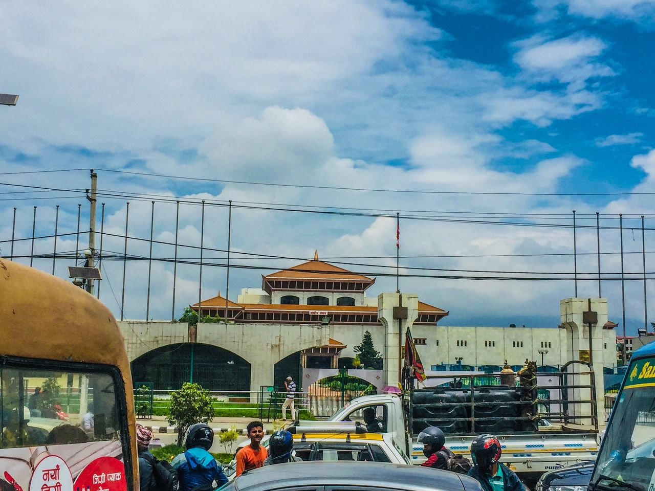 transportation, cloud - sky, mode of transportation, architecture, built structure, car, building exterior, sky, city, motor vehicle, land vehicle, day, group of people, nature, real people, street, men, travel, city life, incidental people, outdoors