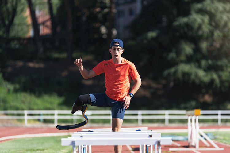 Young athlete with prosthetic leg standing amidst railings on running track