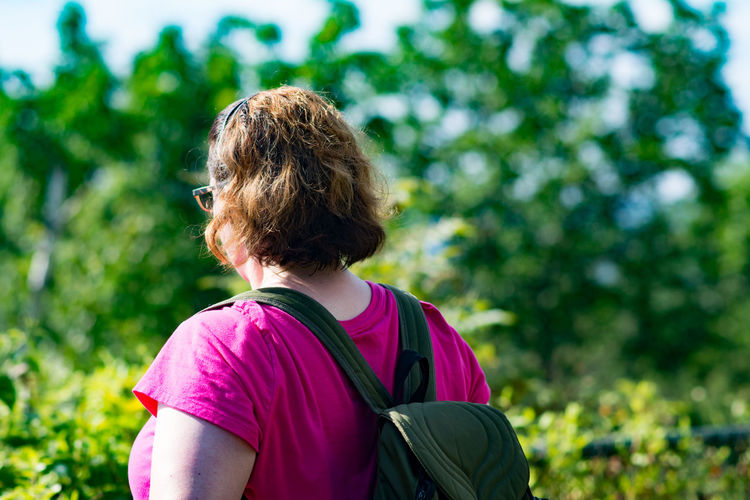 Woman with backpack by plants during sunny day
