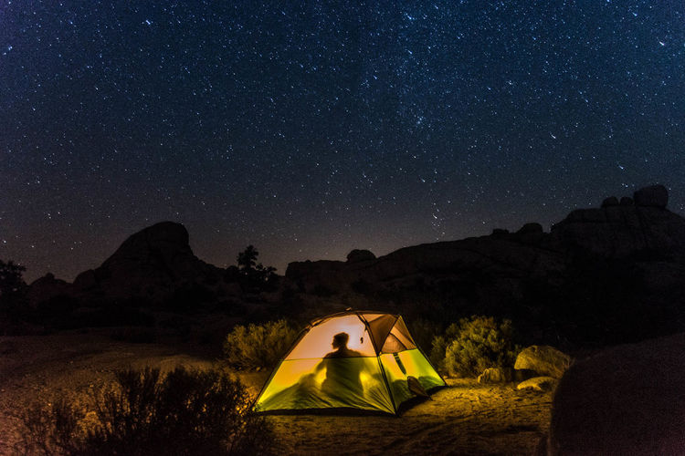 Shadow of person sitting in tent by sky with stars at night