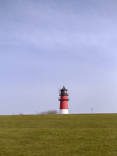 Lighthouse on field against sky