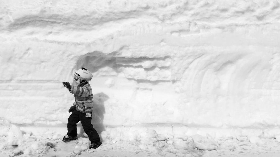 Young boy in ski gear walking along base of snow embankment in a parking lot Black And White Photography Profile Ski Child EyeEm Selects Winter Snow Cold Temperature Weather Real People Full Length Warm Clothing One Person Lifestyles People