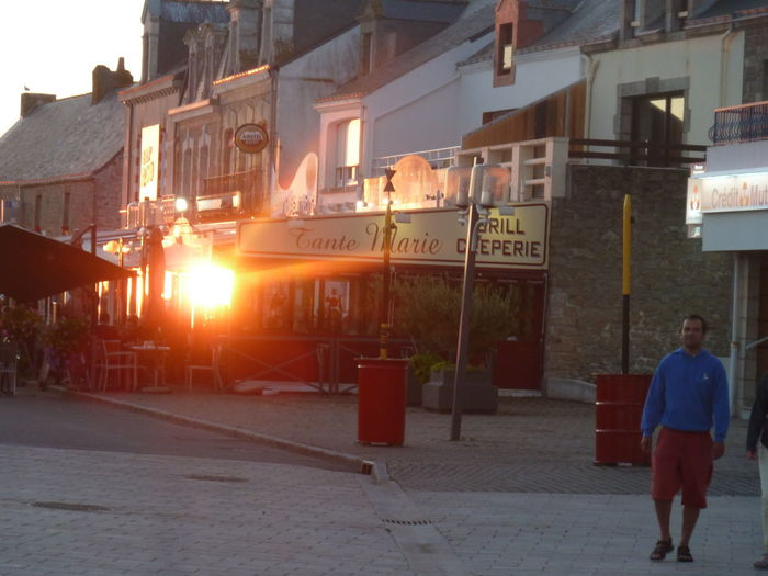 Looking for a restaurant with terrasse Paint The Town Yellow Small Port Summertime Man Surprised Night Falling Sun Reflecting On Shop Window