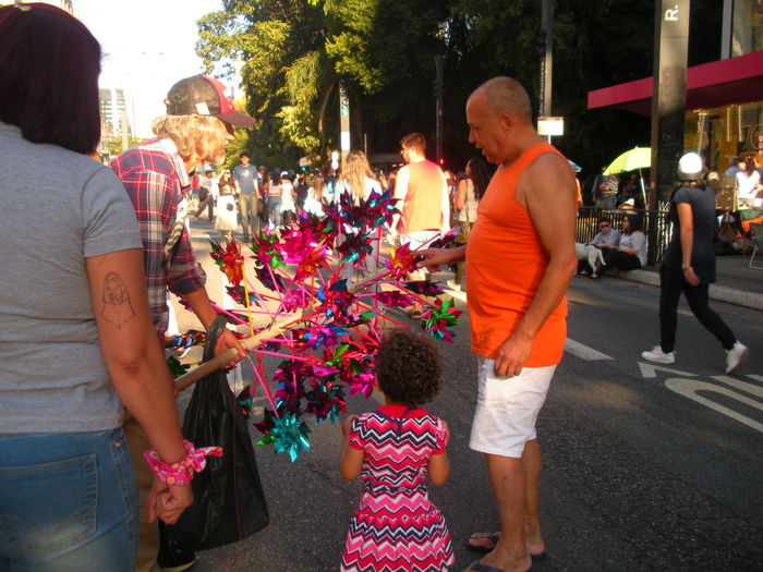 "July 15, 2018 - On Sunday Avenida Paulista is closed off to traffic. This is the day when people take to the street to relax, exercise, walk, jog, ride bicycles, listen to music, have a snack and soak up the sun. In this photo, a man stops to purchase a pinwheel for his daughter, called a ""catavento"" in Portuguese. Avenida Paulista Cataventos City Life Financial District  Pinwheel Small Business Small Business Heroes Susan A. Case Sabir The Photojournalist - 2018 EyeEm Awards The Street Photographer - 2018 EyeEm Awards Unretouched Photography Catavento City Planning cityscapes Downtown São Paulo Emotion Leisure Activity Lifestyles Pinwheel Toy Pinwheels Positive Emotion Real People Togetherness Urban Landscape"