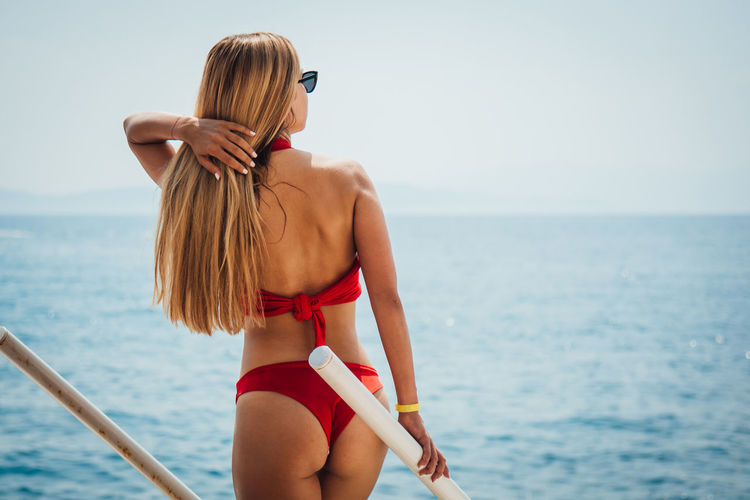 Sea Water Rear View Hair One Person Clothing Swimwear Bikini Lifestyles Hairstyle Horizon Real People Young Adult Leisure Activity Standing Young Women Three Quarter Length Horizon Over Water Fashion Outdoors