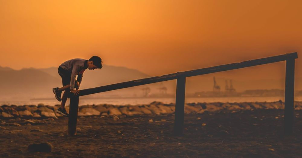 Side view of boy climbing on railing at beach during sunset