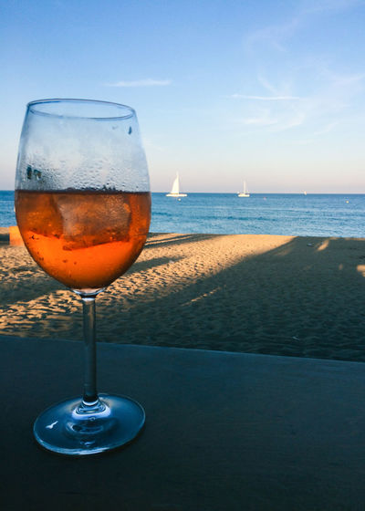 Wineglass on table by sea against sky