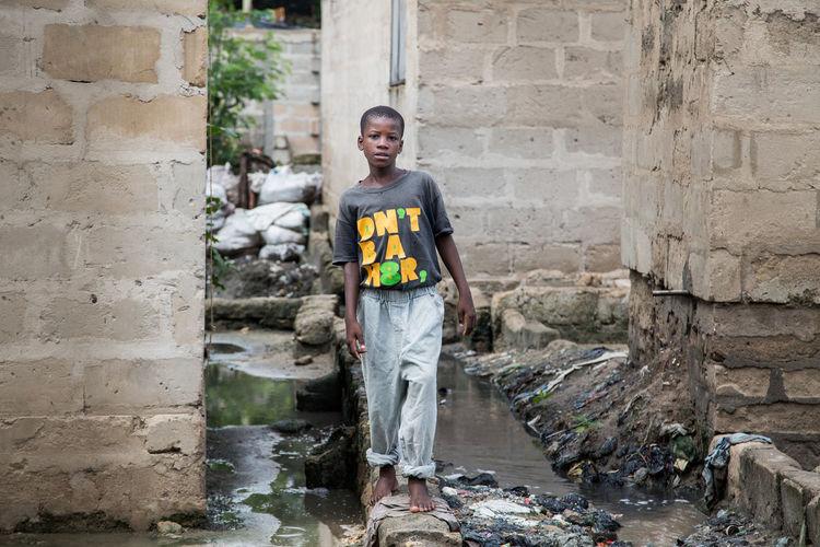 Portrait of teenage girl standing against building