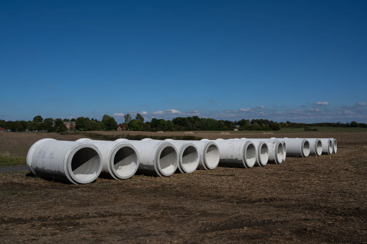 Row of pipes on field against clear blue sky