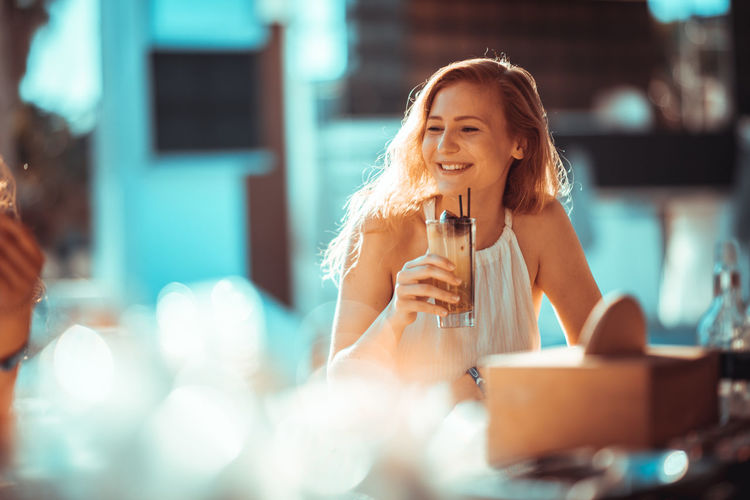 Smiling Young Woman Drinking At Restaurant
