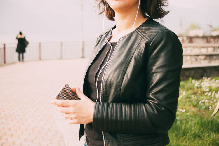Midsection of woman holding smart phone while standing on mobile