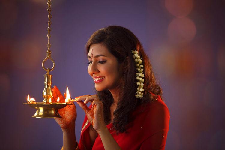 Beautiful indian woman in red sari lighting diya during diwali