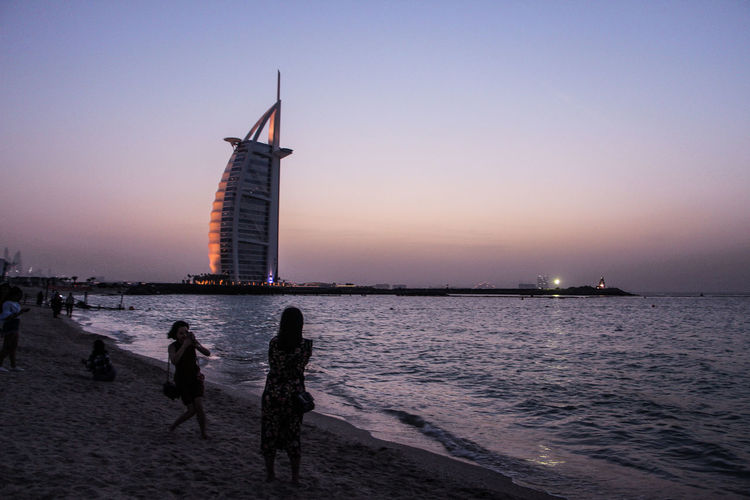 Water Sky Sunset Sea Beach Nature Architecture Built Structure Real People Dusk Land Beauty In Nature Building Exterior Clear Sky Scenics - Nature Lifestyles People Leisure Activity Silhouette Dubai Burj Al Arab