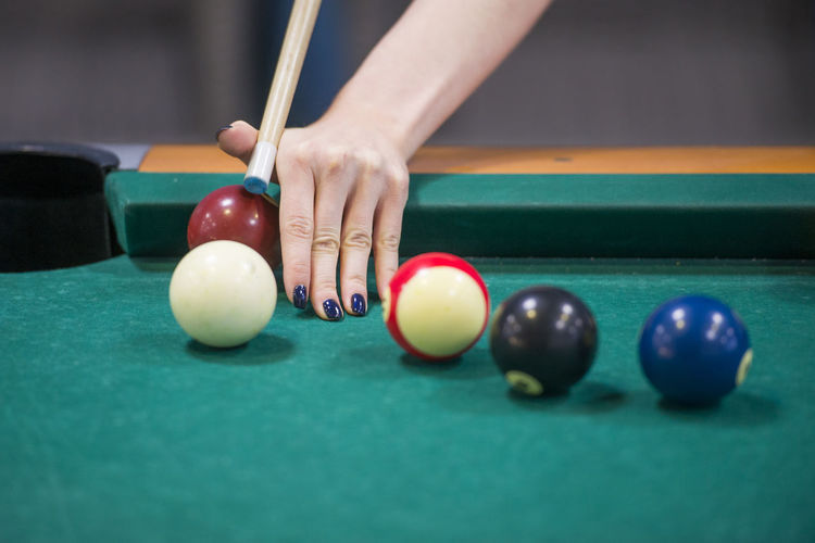 Cropped hand of woman playing pool on table