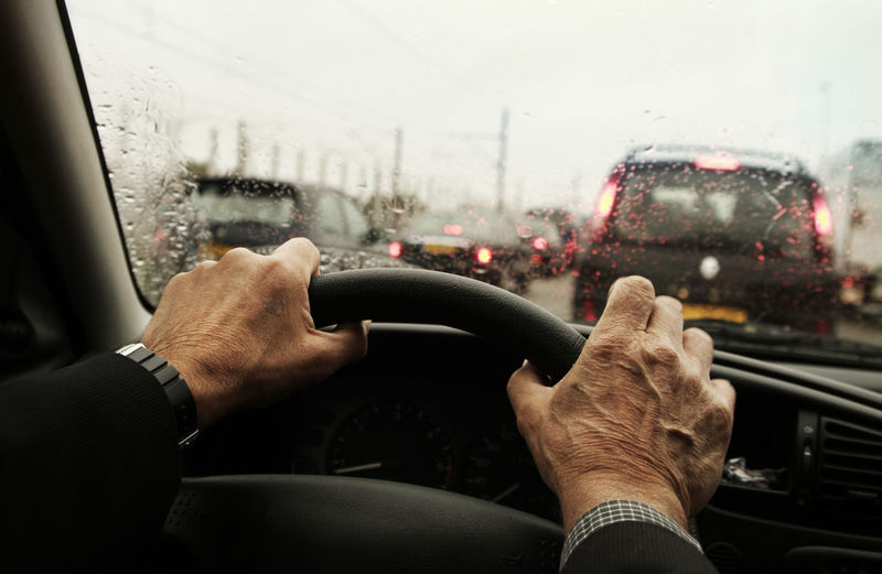Close-up of man hand holding car windshield