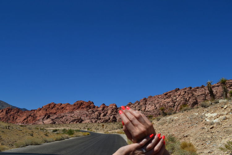 Woman's Hands Against Country Road
