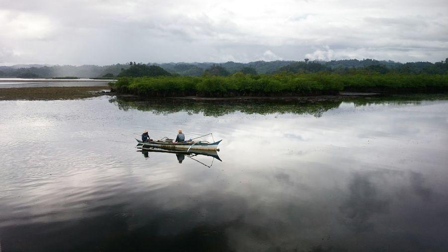 Boat Sailing In Lake Against Sky