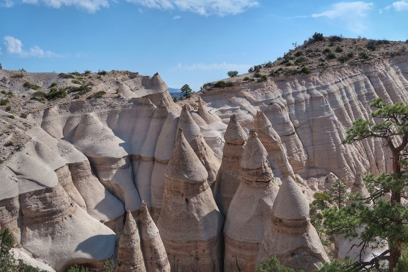 High angle landscape of triangular rock formations in in Kasha-Katuwe Tent Rocks National Monument in New Mexico Kasha-Katuwe Tent Rocks National Monument New Mexico Sky Nature Rock Formation Sunlight Day No People Solid Beauty In Nature Tranquility Scenics - Nature Rock Rock - Object Land Plant Tranquil Scene Geology Outdoors Cloud - Sky Non-urban Scene Travel Destinations The Great Outdoors - 2019 EyeEm Awards