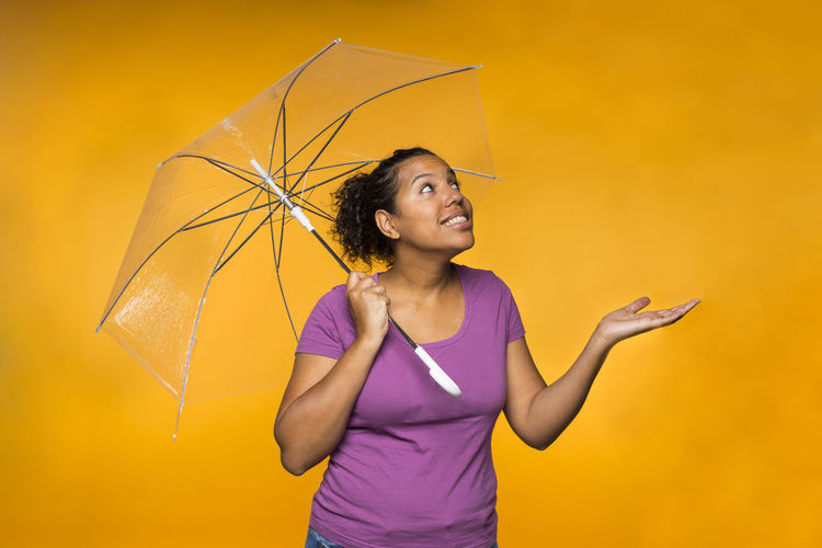Smiling Woman Holding Umbrella While Standing Against Orange Background