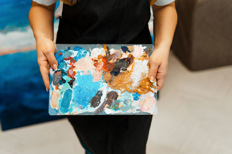 Midsection of woman holding messy palette
