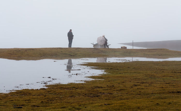 couple playing in the fog.. Couple Adult Adults Only Adventure Beauty In Nature Day Fog Grass Lake Mountain Nature Outdoors People Plastira Lake Puddle Salt Basin Scenics Sky Standing Togetherness Two People Vacations Walking Water Winter Lost In The Landscape