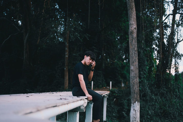 Young man sitting on bridge against trees in forest