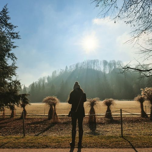Full length rear view of woman standing in field against sky on sunny day