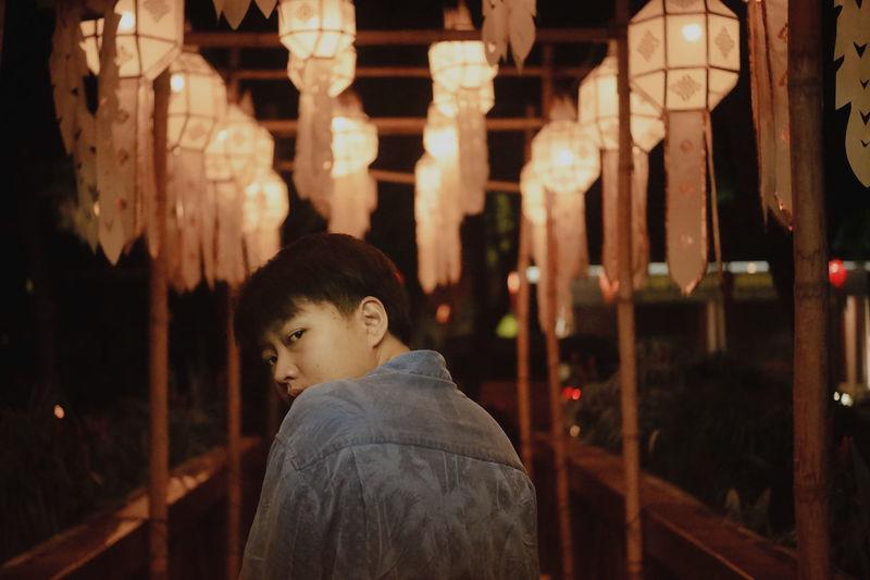 Rear view of man looking at illuminated lamp at night