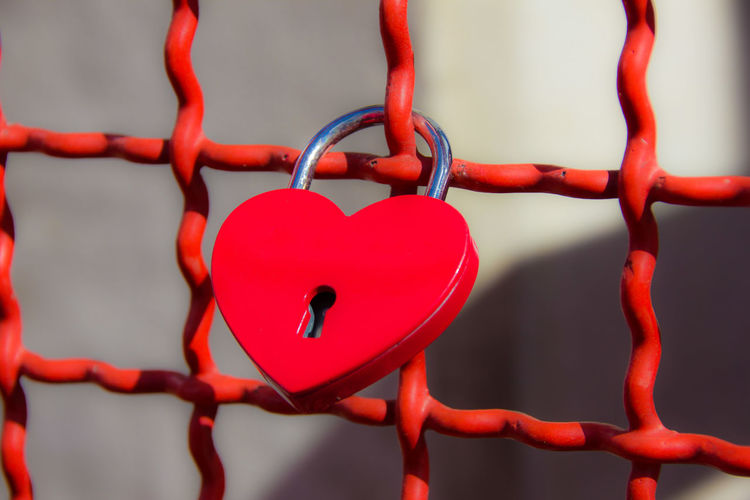 Close-up of love lock hanging on fence