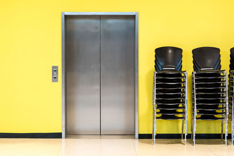 Krull&Krull Architecture Architecture Door Elevator Wall Day Minimalism Yellow Chairs Minimalistic Indoors  Stacked Metal No People Yellow Background Piled Indoors  Krull&Krull Minimalistic