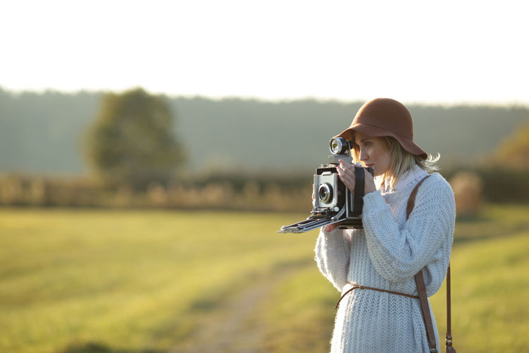 Woman photographing through camera while standing on field