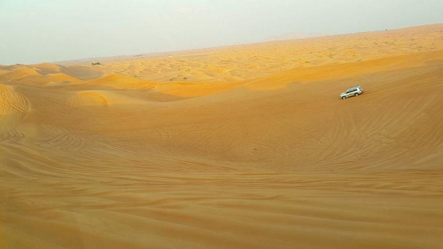 Car in desert against sky