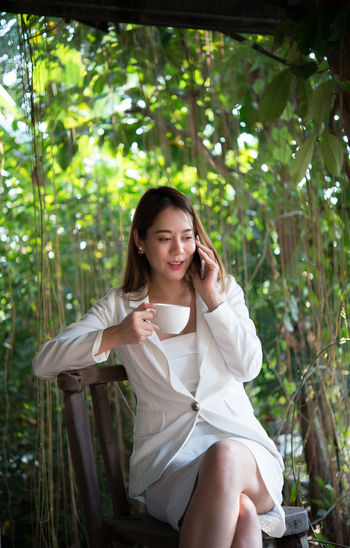 Businesswoman holding coffee cup while talking on mobile phone