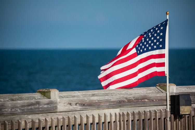 Flag by sea against blue sky