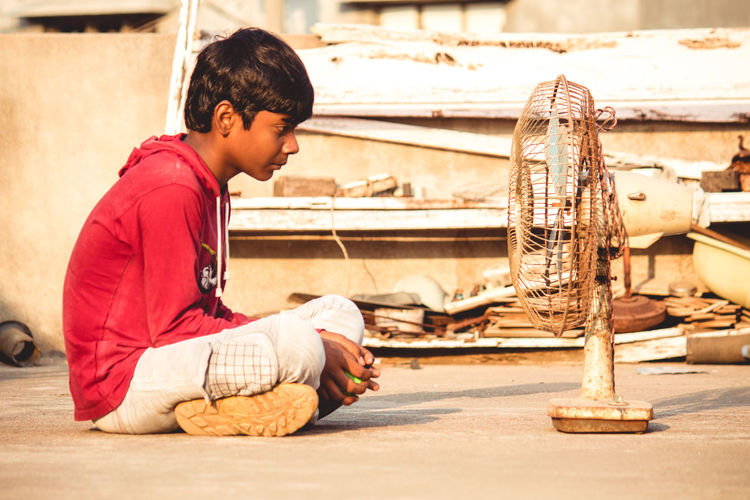 Boys Casual Clothing Child Childhood Day Focus On Foreground Full Length Holding Lifestyles Males  Men One Person Playing Profile View Real People Side View Sitting Teenager Water