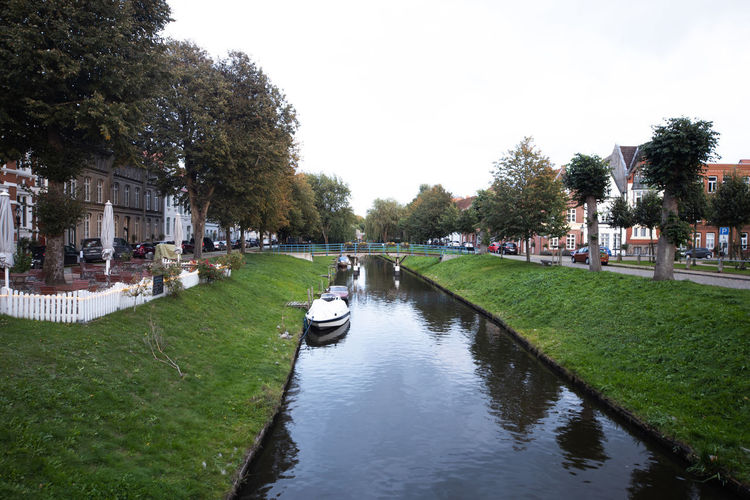Canal in park against sky in city