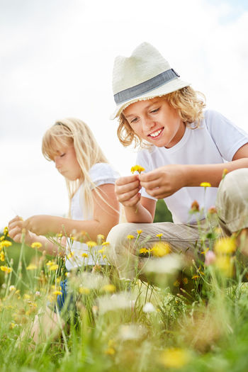Smiling Boy Holding Flower While Sitting With Sister On Field Against Sky