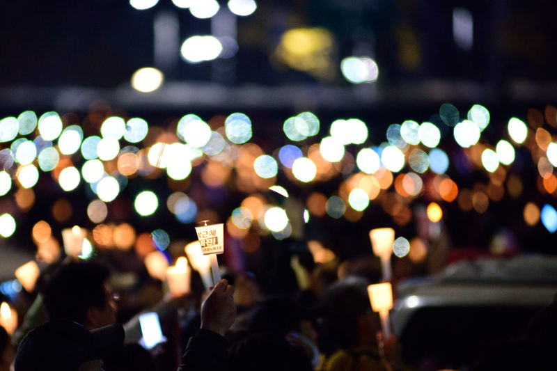 People With Candles Marching At Night