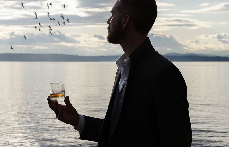 Man holding whiskey glass while standing against sea during sunset