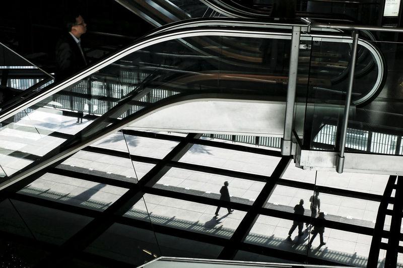 Businessmen On Escalator And Footpath