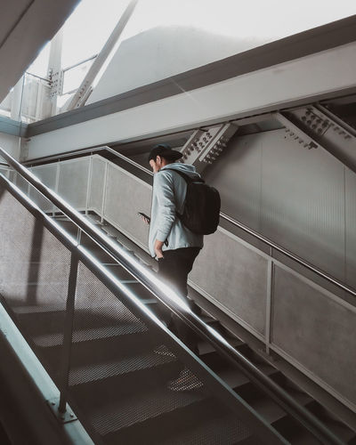 Low angle view of man standing on escalator