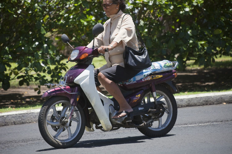 Business Woman Riding Motorbike - Rarotonga, Cook Islands, Polynesia, Oceania Adult Bag Bike Blouse Business Businesswoman Casual Close-up Cook  Driving Elégance Elegant Fashion Glasses Handbag  Handlebar Holding Honda Islander Islands Journey Mature Moped Motion Motor Motorbike Motorcycle Nature Pacific People Polynesia Polynesian Portrait Profile Rarotonga Riding Road Scooter Sitting Street Summer Tourism Traffic Transportation Travel Tropical Tropics Vacation Vehicle Woman Mode Of Transportation Real People Ride Leisure Activity Casual Clothing Land Vehicle Day Lifestyles Sunlight Plant Full Length Outdoors