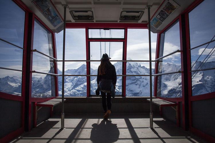 Rear View Of Women Looking Towards Snowcapped Mountains Through Ski Lift Windows