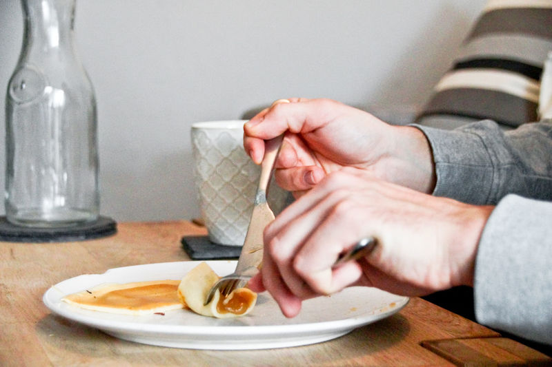 Cropped hand eating food on table