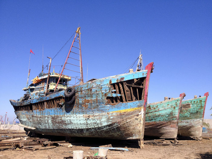 Abandoned boats against blue sky