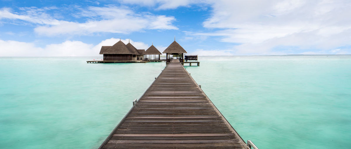 Water Bungalows on the tropical lagoon in Maldives Beauty In Nature Blue Boardwalk Bungalow Cloud - Sky Day Maldives Nature Ocean Outdoors Paradise Relax Resort Scenics Sea Sky Water