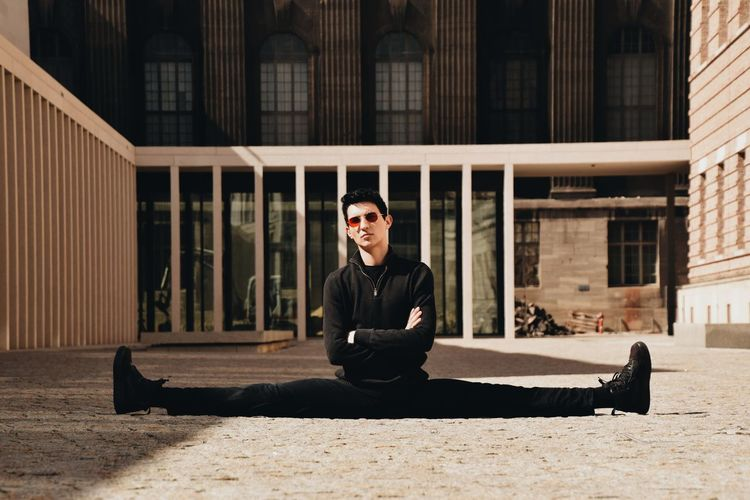 Full length portrait of young man sitting outdoors