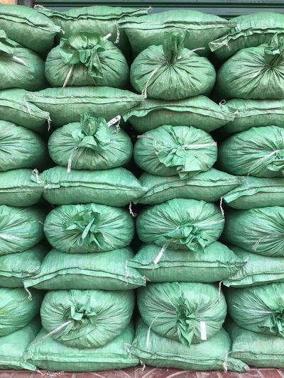 Heap Sand Bag Full Frame Backgrounds Large Group Of Objects Abundance No People Stack Arrangement Repetition Green Color Day Industry For Sale Pattern Order