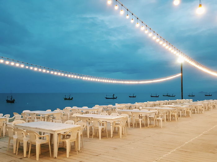 The romantic evening dining place decorated with the warm lamps and sea view